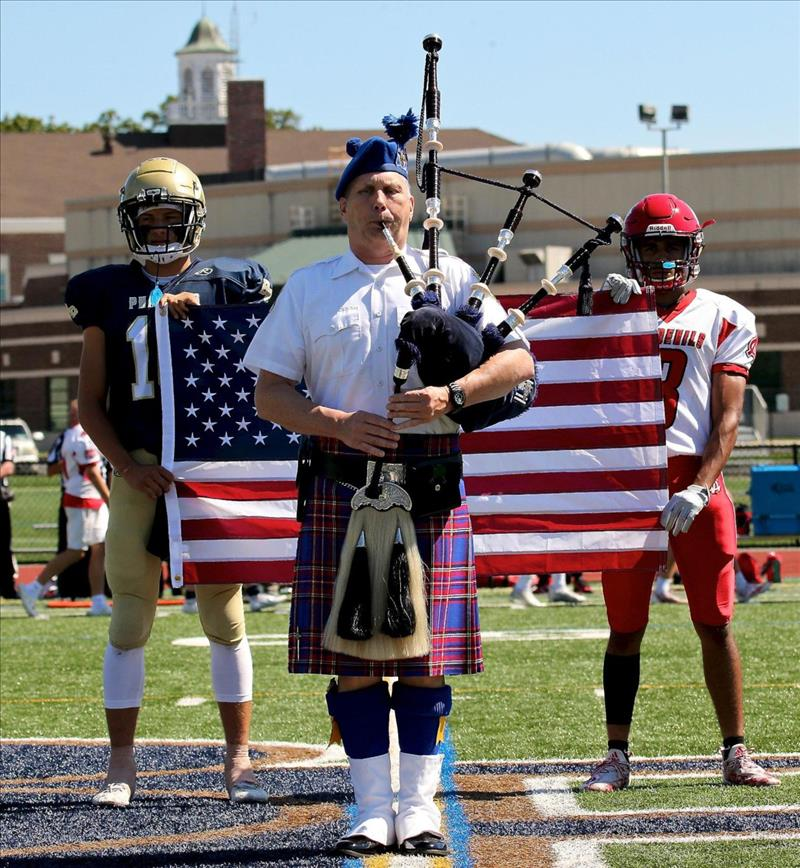 Bagpiper Frank Howard, BBP Brady Clark and Center Moriches' Judah Williams at midfield during the 9/11 ceremony before the start of Suffolk Division IV game on Saturday, Sept. 11, 2021 at BBP. (credit: George A. Faella)